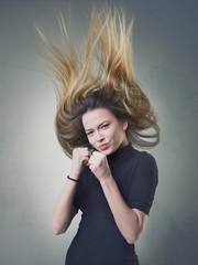 Jumping girl with flying ombre hair and clenched fists