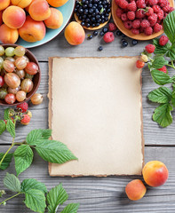 Open recipe book with fresh fruits and berries on wooden background. Copy space, top view, high resolution product.