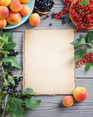 Old paper with fresh fruits, berries and branches with currant  on wooden background. Close up, top view, high resolution product.