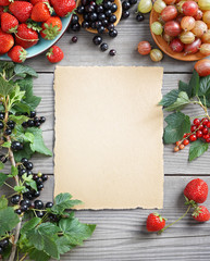 Sheet paper with fresh  berries and branches with currant on wooden background. Copy space, top view, high resolution product.