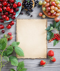 The berries, green leaf and old paper on wooden background. Copy space for your text. Top view, high resolution product.