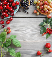 Cherry, gooseberry, currant and green leaves on wooden table. Top view, high resolution product. Harvest concept.