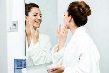 Young woman caring of her skin standing near mirror in the bathr