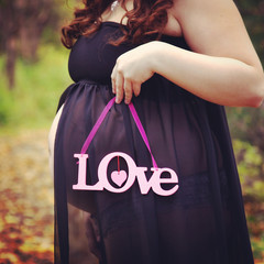 beautiful instagram of pregnant woman holding quote forest path
