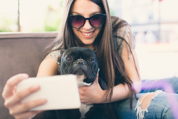 Beautiful young girl taking selfie with her French bulldog pet.