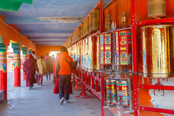 Buddhist nun walking touch a prayer wheels around the sanctuary at Larung gar (Buddhist Academy) in Sichuan, China. This is the public place