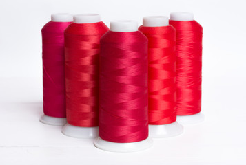 Red bobbin thread on white wooden table