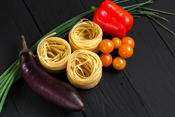 pasta and vegetables on black background