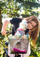 Pretty girl with bicycle and Maltese dog