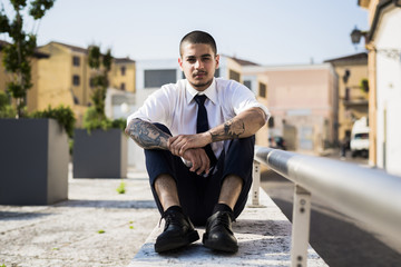 Portrait of young businessman with tattoos on his forearms sitting on a wall