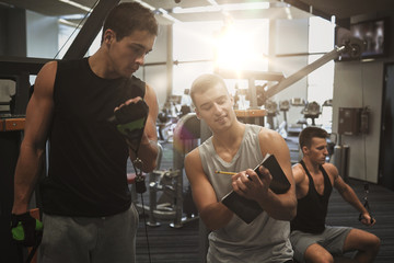 men exercising on gym machine