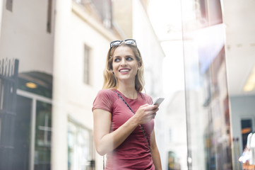 Portrait of smiling woman with smartphone standing in front of shop window