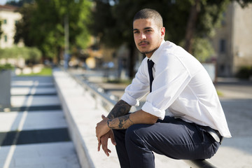 Portrait of young businessman with tattoos on his forearms sitting on railing