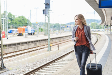 Young woman with smartphone and wheeled luggage walking at platform