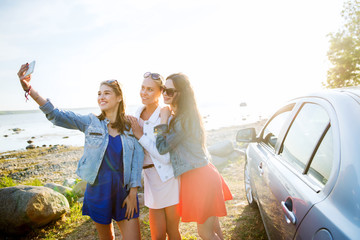 happy women taking selfie near car at seaside