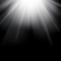 Shiny sunburst of sunbeams on the black background.