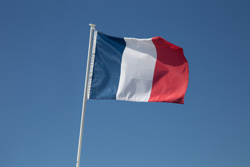 French flag is waving in the wind, on the blue sky