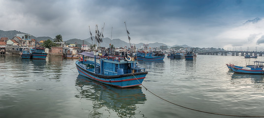 Vietnam, Nha Trang. May 1, 2015. Panorama. Fishing village. Ship and boat. Sunrise over a bridge across the Cai River.