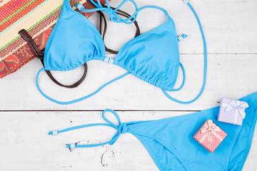 blue swimsuit, bag and gift boxes on white wooden desk