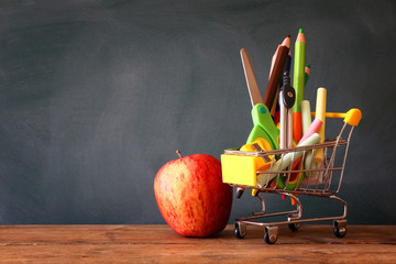 Shopping cart with school supply and apple