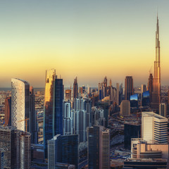 Big modern city with futuristic architectrure at sunset. Beautiful aerial cityscape with skyscrapers. Dubai, UAE. Travel background.
