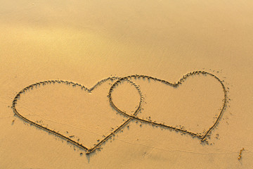 Two lovers hearts drawn on the sand to the sea.