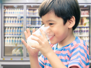Little boy drinking fresh milk for healthy background of UHT milk storage