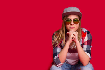 Young beautiful woman in checkered shirt. Red background. Copy space