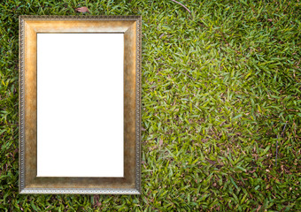 Golden antique frame on rustic grass garden background.