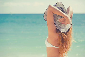 Beach vacation. Woman in sunhat bikini standing with her arms raised to head