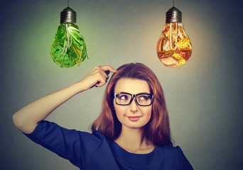 Woman thinking deciding on diet looking up at junk food vegetables light bulbs