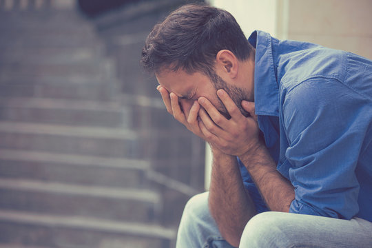 stressed sad young crying man sitting outside holding head with hands