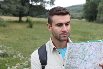 Handsome male looking at map and planning trip after getting lost alone in the woods
