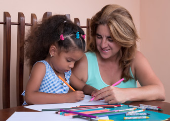Small multiracial girl and her mother drawing with color pencils