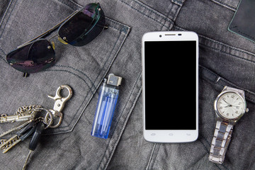 Smart phone, sunglasses and watch on jeans background