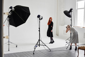 Girl photographer photographing fashion model in black color on white background in Studio