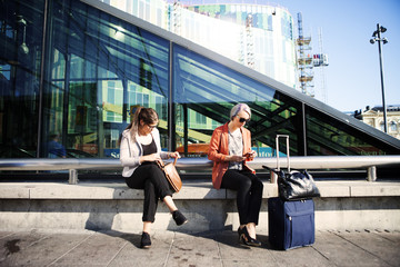 Two women sitting on bench at train station