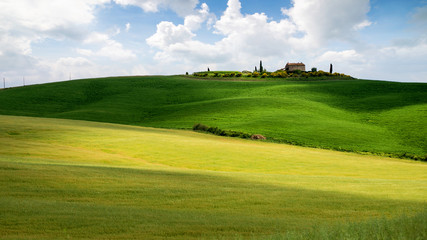 Tuscany landscape, small house on top of a hill against blue sky
