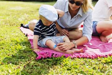 Mother putting bandage on son's leg during picnic in park