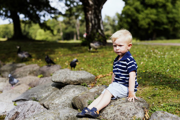Full length of boy sitting on rock in park