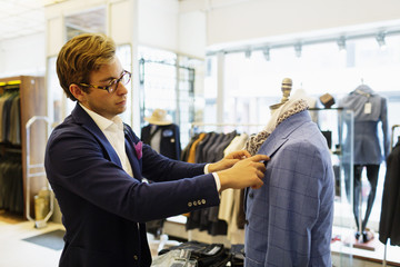 Designer fixing suit on mannequin at clothing store