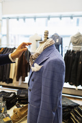 Cropped image of designer's hand reaching mannequin in clothing store