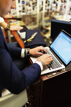 Cropped image of salesman using laptop in clothing showroom