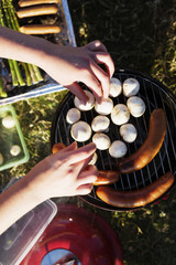 Cropped image of hands cooking mushrooms and sausages on barbeque