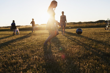 Friends playing football on field during sunset