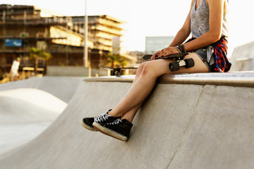 Low section of teenage girl with skateboard sitting at the edge of ramp in skate park