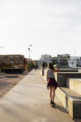 Full length rear view of teenage girl skateboarding in skate park