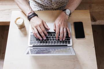 Hands of man using laptop