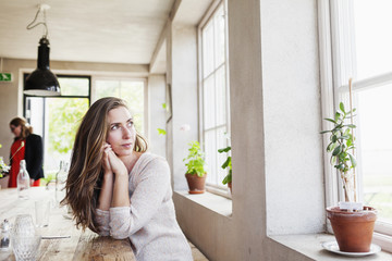 Thoughtful woman looking away while sitting at restaurant table during coffee break