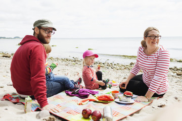 Family enjoying picnic at beach